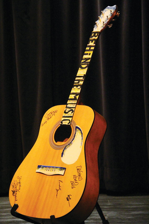 "A stringless guitar inscribed with the phrase ""Behind the music"" on its neck Oct. 3 at The Forum Theater in Koelbel Library in Centennial. The organizer of the library's songwriter showcase — which emphasizes performers telling the stories behind the songs they play — intends for the musicians to sign the guitar and plans to donate it to the library."