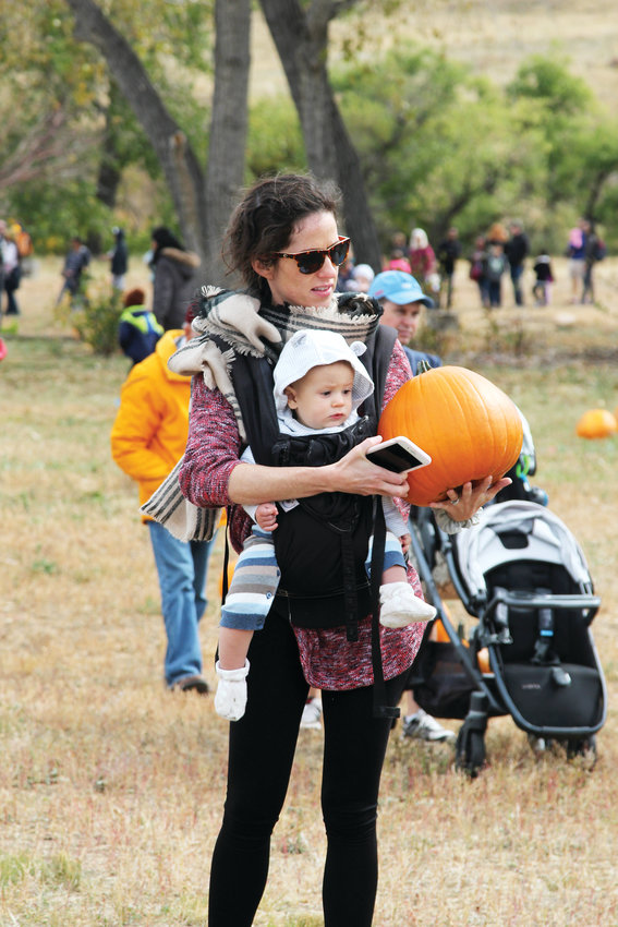 Rachel Gingrich balances a pumpkin and 9-month-old Leighton while visiting the Schweiger Ranch Fall Festival on Oct. 6.