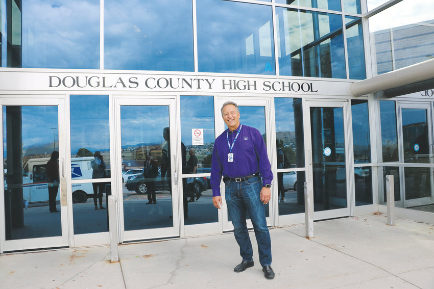 Douglas County High School Principal Tony Kappas stands in front of his school in Castle Rock. One of DCSD's oldest, the school has a long list of Tier 1 needs, which are critical building repairs that risk safety.