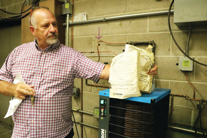 Wayne Blazek, facilities planning manager at Douglas County School District, holds an outdated manual in a boiler room at Ponderosa High School in Parker. A bond would help address the school's heating and cooling systems.