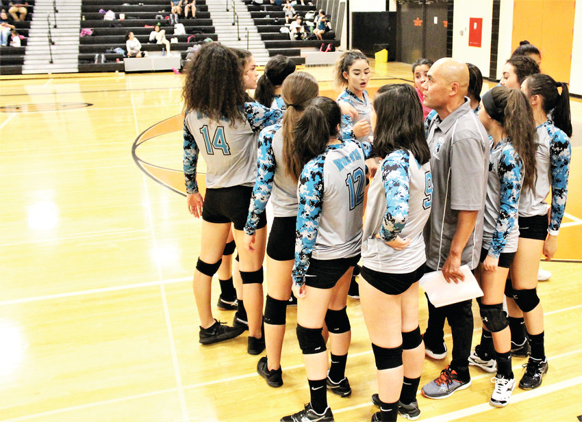 The Lady Wolves, led by coach Marcel Bandera, break the huddle after a timeout at Gateway Oct. 3.