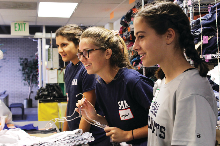 Adrianna Stefanoudakis, left, Marygrace Adam and Lauren Sottosanti sort through hangers at the Clothes to Kids of Denver shop. The girls came to volunteer at the nonprofit with their school, St. Mary's Academy.