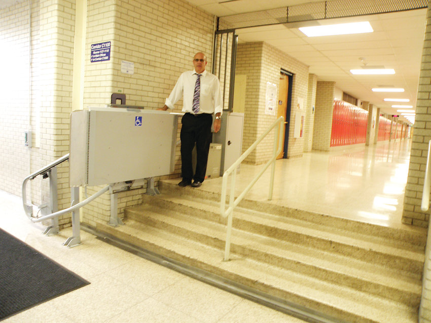 Newton Middle School Principal James O'Tremba stands beside an electric wheelchair lift that traverses a four-stair rise, which he said can take eight to 10 minutes to utilize. Newton is one of the schools that would see a rebuild offering better disabilities access if voters approve Littleton Public Schools' nearly $300 million bond issue this fall.