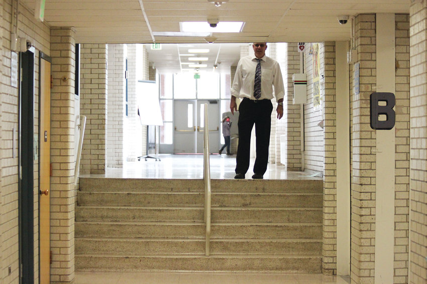 Newton Middle School principal James O'Tremba stands atop a short staircase without an electric wheelchair lift, which forces wheelchair users to make a lengthy detour.