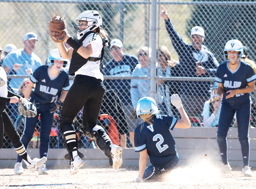 Rock Canyon catcher Katie Dack-Howell (18) leaps for the inbound catch at home as Valor Christian's Eden McNally (2) crosses the plate. The Jaguars took 1st place in 5A region 2 Saturday at Northridge Park by the score of 11-3. The Jaguars also defeated Chatfield 6-1 in the earlier game.