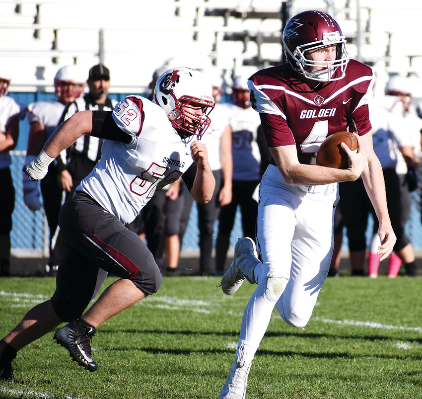 Golden senior quarterback David O'Connell (4) scrambles away from Chatfield senior defensive lineman Ben Iverson (52) during the first half Friday, Oct. 12, at the North Area Athletic Complex. The Demons suffered a 36-19 loss.