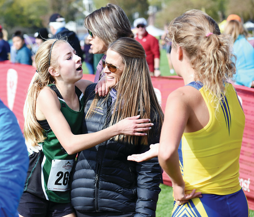 D'Evelyn sophomore Taylor Haerbig leans on a familiar face, D'Evelyn athletic trainer Toni Sampson, after finishing fifth during the Class 4A girls race at the Jeffco League cross country championships Thursday, Oct. 11, at Clement Park. The Jaguars claimed the 4A Jeffco girls team title edging Green Mountain by a single point.