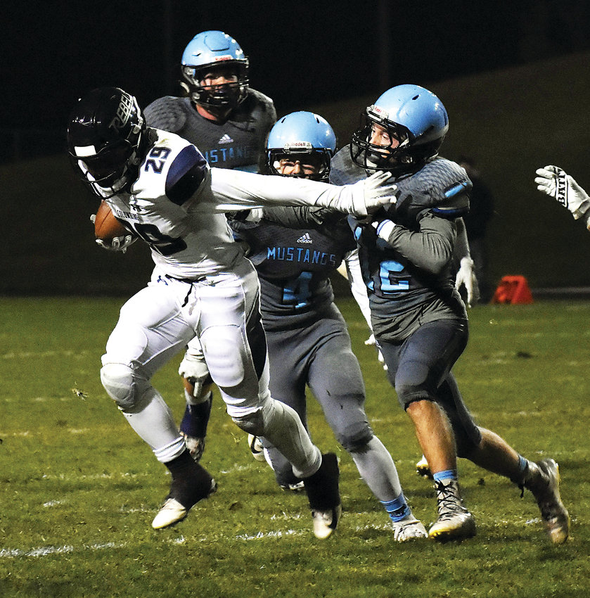 Ralston Valley senior Tanner Spirek (12) and junior Kaleb Tischler (4) attempt to bring down Columbine junior running back Adam Harrington (29) during the Class 5A Metro West League game Thursday, Oct. 11, at the North Area Athletic Complex. The Mustangs loss to the Rebels 29-14.