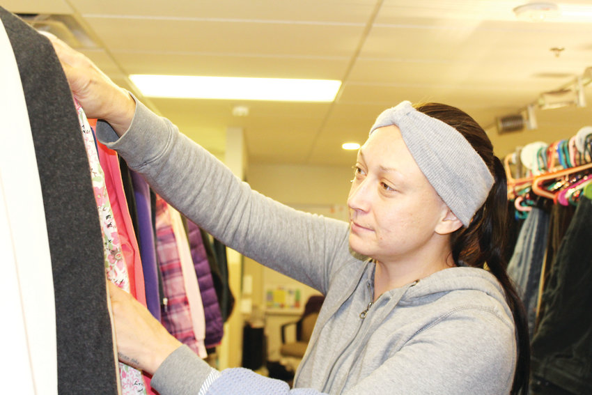 Sarah Copenhaver glances at clothes at The Action Center in Lakewood.