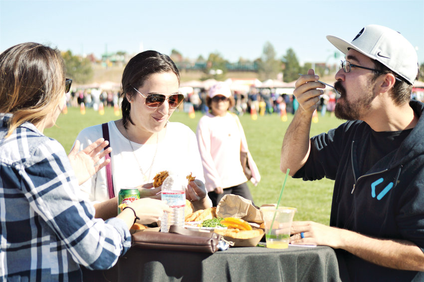 Britny Bridgham, of Littleton and Laurie Cagney and Daniel Caetano of Parker enjoy some Brazilian food truck fare Oct. 20 at Westminster's HarvestFest in the Westminster Downtown. Crowds of people, costumed and otherwise, came to the fall fair for sun, food and music.