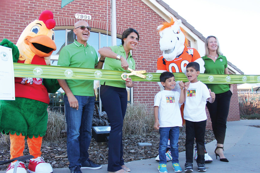 From left, Primrose School mascot Percy, school owners Reza and Farima Nemat, their two sons Kurosh and Shaheen, Broncos mascot Miles, and Primrose School director Delise Evans cut the ribbon on the school's new sustainability and security efforts.