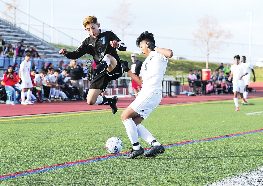 Rangeview defender Ivan Serrano, right the light jersey, takes the ball from Mountain Range's Brayan Fernandez, during first half action of a CHSAA Boys 5A playoff game Oct. 25 at District 12 North Stadium in Westminster.  The visiting Raiders defeated the Mustangs, 3-2.