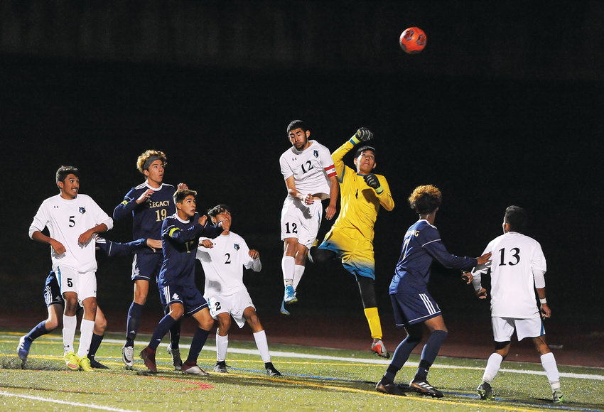 Westminster goalkeeper, Fernando Gomez Macias, right, and teammate Brian Aguirre (12), head away a Legacy corner kick, late in the first half of the CHSAA Boys 5A playoff game at District 12 North Stadium Oct. 25. Gomez Macias made several stellar saves in the half, but Legacy tallied the game's only goal in the 2nd period, to advance in the tournment, 1-0.