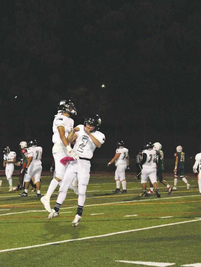 Wolves' senior Matt Harris and junior Romeo Rodgriguez celebrate a touchdown Oct. 26 against Smoky Hill at the Stutler Bowl.