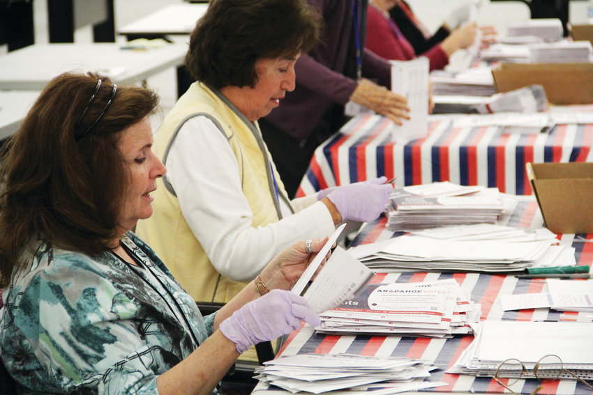 Kathleen Mendelson, left, helps look through ballots during the sorting process Nov. 1 at the Arapahoe County Elections Facility. Dozens came to a tour of the facility at 5251 S. Federal Blvd. in Littleton that night to watch how ballots already returned for the Nov. 6 election are processed.