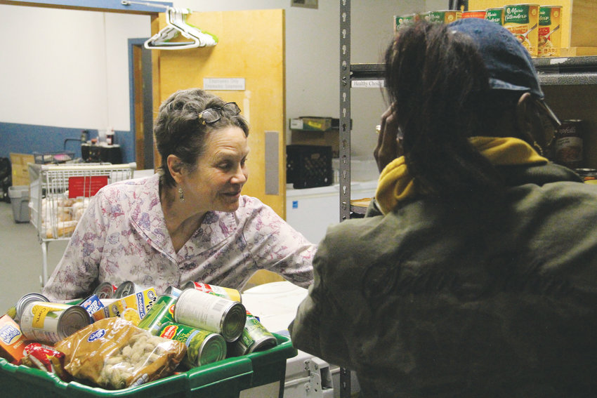 Margie Carroll, a volunteer at Integrated Family Community Services, helps a client get food Oct. 30 at the building's food pantry. The organization sits at 3370 S. Irving St. in the Sheridan area.