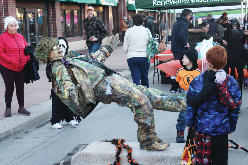 A statue comes to life and performs balancing acts for the kids during Parker's Trick-or-Treat on Mainstreet event Oct. 31.