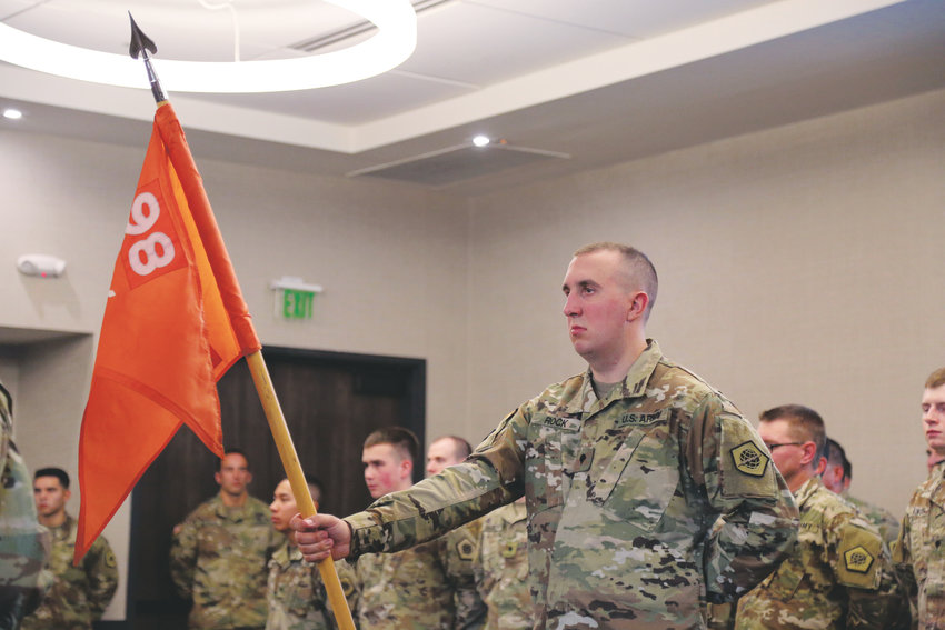 Specialist Alan Rock holds the flag for the 98th Signal Battalion during a deployment ceremony held Nov. 4.