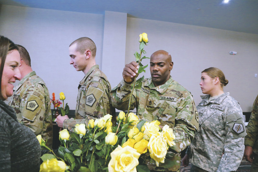 Alpha First Platoon, Platoon Sgt. Lawrence Washington picks a flower given to deploying soldiers for their loved ones. photos by shanna Fortier