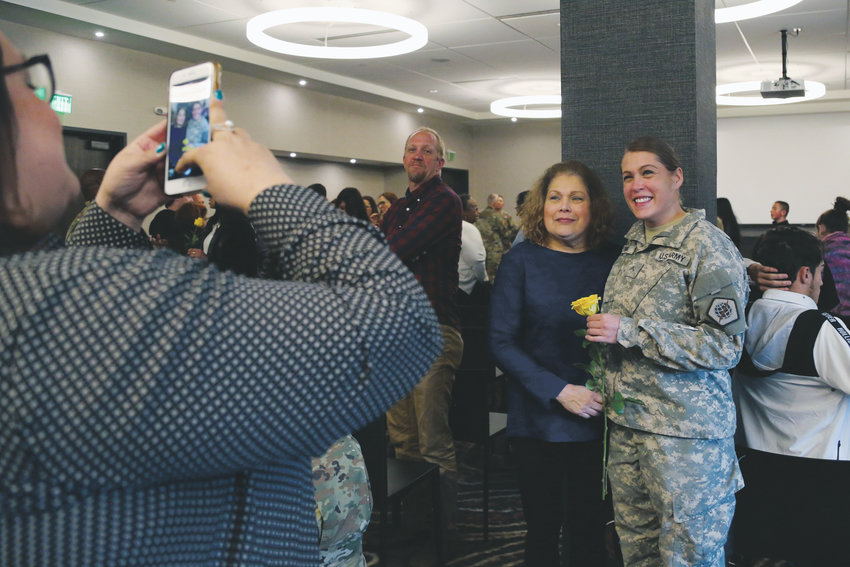Private Emily Young takes a photograph with her mother, Yolanda Loran, following the deployment ceremony for the Alpha Company of the 98th signal battalion of the U.S. Army Reserve.