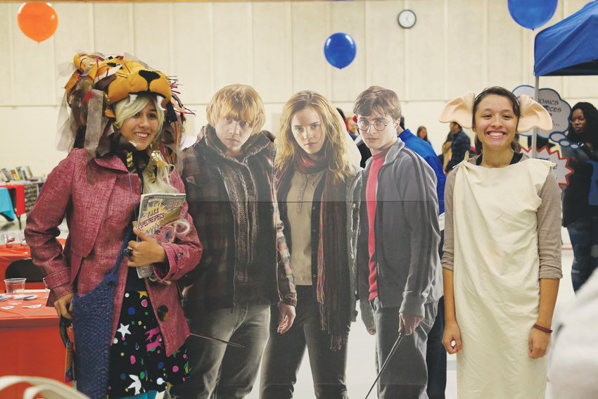 "Dressed as Luna Lovegood and Dobby, sisters Mariah and Tayla Mendoza pose with a cutout of the three leading characters from the ""Harry Potter"" series."
