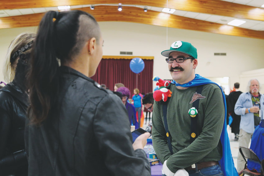 Dressed as Luigi, Grayson Stamm, patron experience supervisor for Jeffco Libraries, gives clues for the murder mystery being solved by Fandomonium attendees.