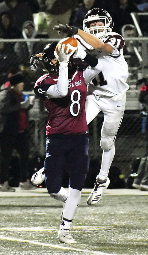 Dakota Ridge senior Justin Sanchez (8) is able to make a catch despite the effort of Golden junior Dylan Mathias during the Class 4A Jeffco League finale for the Demons on Nov. 1 at Trailblazer Stadium. Golden jumped out to a 14-0 lead, but eventually lost 34-17 to end the season for the Demons.