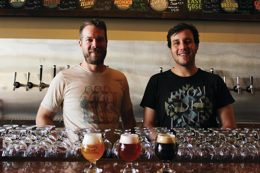 Brewer Brian Grace, left, with his assistant brewer James McPherson, stand behind the bar at Thirsty Monk Brewery in Uptown. The brewery opened earlier this year, and recently won a medal from the Great American Beer Festival.