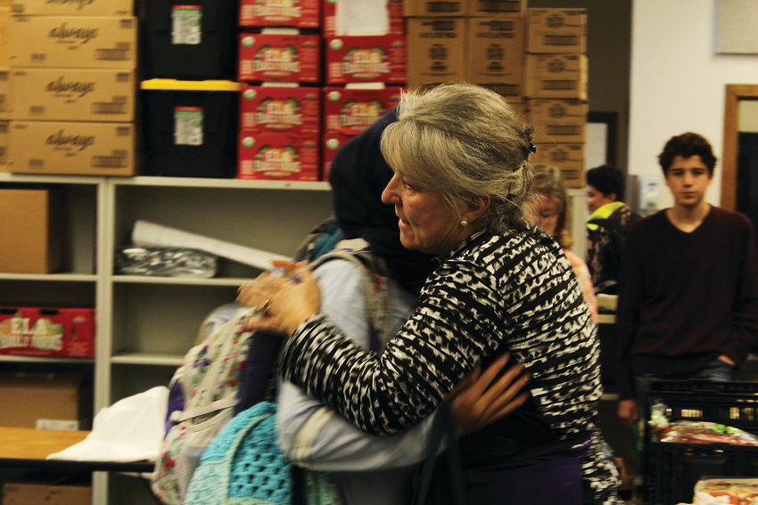 Jaclyn Yelich hugs a student at the South High School food bank. Yelich started the food bank four years ago with her husband.