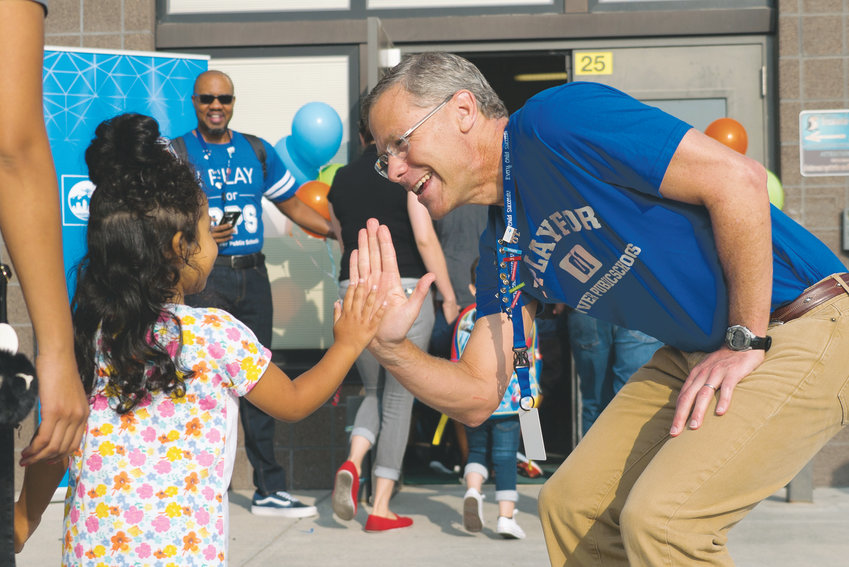 Tom Boasberg, former superintendent of Denver Public Schools, gives a high five to a student on the first day of school at Escalante-Biggs Academy in north Denver.