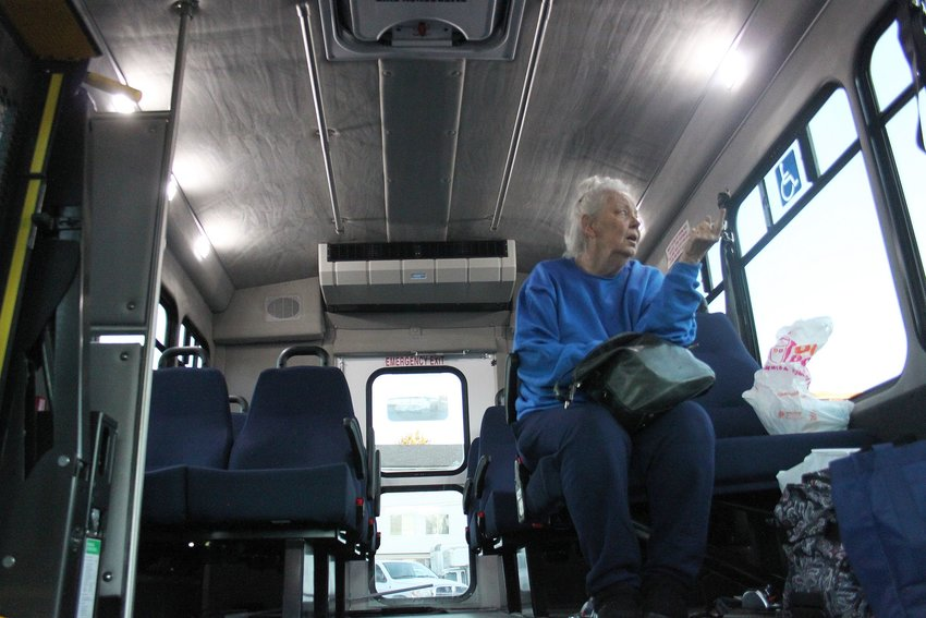 Jane Sterling-Price, 76, boards a bus bound for a hotel after the closure of a Red Cross shelter where she's been staying, since a fire forced the evacuation of the Windermere apartments on S. Datura St. on Nov. 17. Photo by David Gilbert