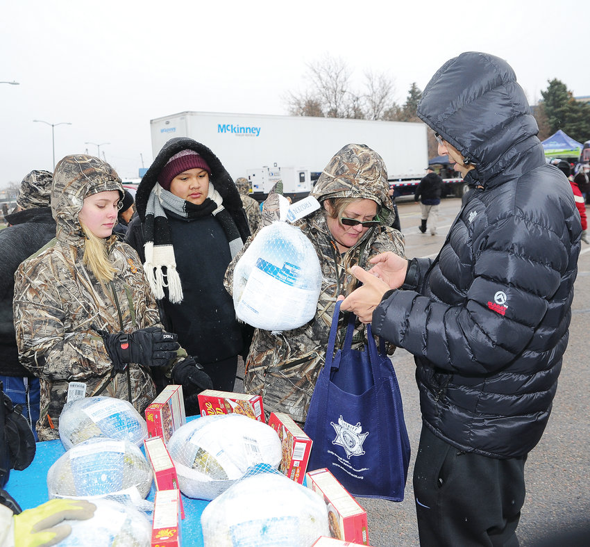 Volunteer Lisa Golden of Brighton, second from right, gives a turkey to Basanta Gyawali of Broomfield, during this year's Operation Freebird, which the Adams County Sheriff's Department held at Water World Nov. 17. Golden was a volunteer with New Hope Ministries. Gyawali is originally from Nepal.