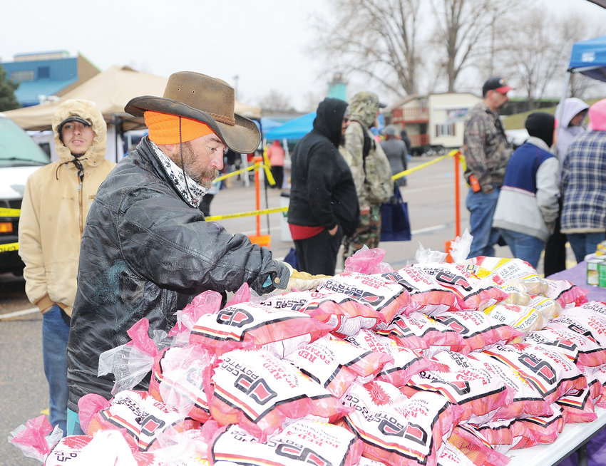 Rick Morgan of Commerce City selects a bag of potatoes, among the many food items given out at this year's Operation Freebird, sponsored by the Adams County Sheriff's Department at Water World Nov. 17.