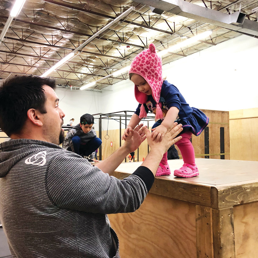 Ken Arrington plays with daughter Addie at Path Movement in Littleton. Arrington founded Path Movement in 2013.