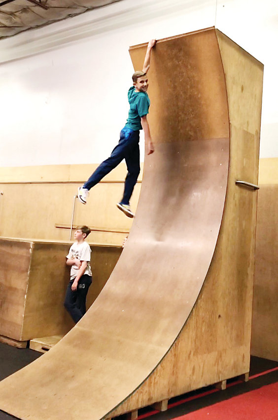 "Ayden Perkins, 14, scales Path Movement's warped wall, a replica from the popular television show ""American Ninja Warrior."" Perkins has been training at Path Movement in Littleton for around four years."