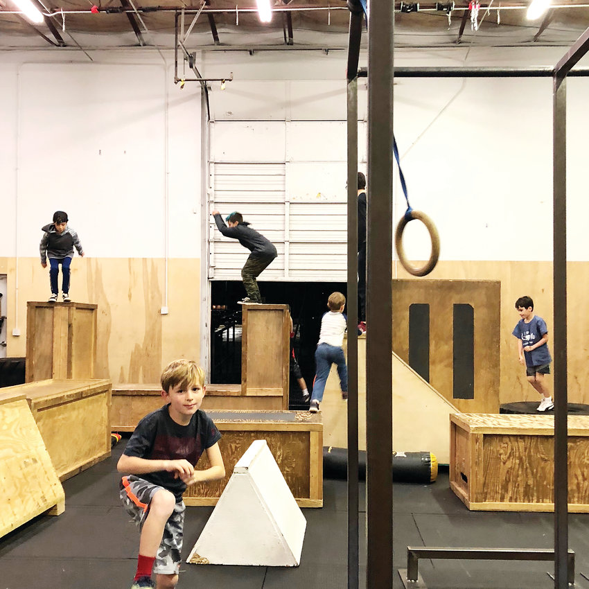 "Students practice their parkour skills during a class at Path Movement. Like many parkour gyms, the Littleton operation consists of a mixture between classes taught by coaches and ""open train sessions"" in which students have more freedom to choose what to practice."