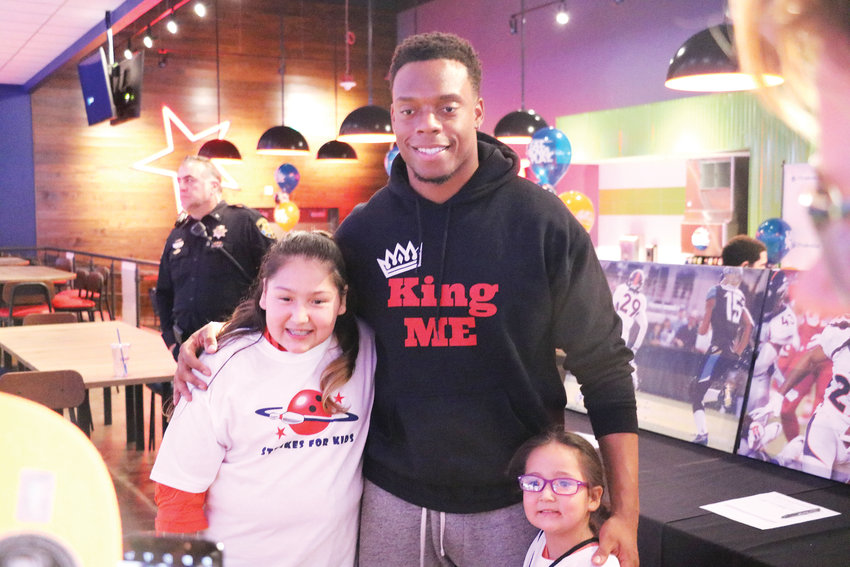 Denver Broncos linebacker Brandon Marshall poses for a photo with Jade Vigil, 11, left, and her sister Remy, 4. Marshall made a special appearance at the fifth annual Orange & Blue Bowling Bash at Main Event Entertainment on Nov. 20. Proceeds from the fundraiser went to the Denver Broncos Boys and Girls Club, which assists children in need across the Denver metro area.