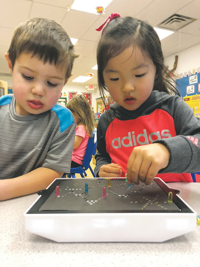 Rowan, 3, and Emily, 4, play with the Lite Brite in the 3 and 4-year-old classroom at The Goddard School of Castle Rock.