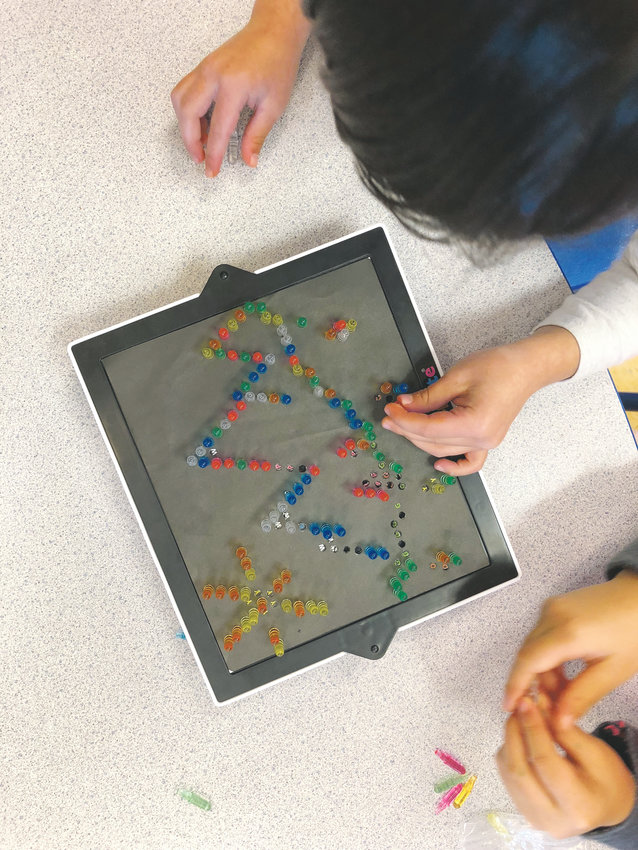 Students at The Goddard School of Castle Rock play with the Lite Brite, this year's winning toy in the school system's annual toy testing program.