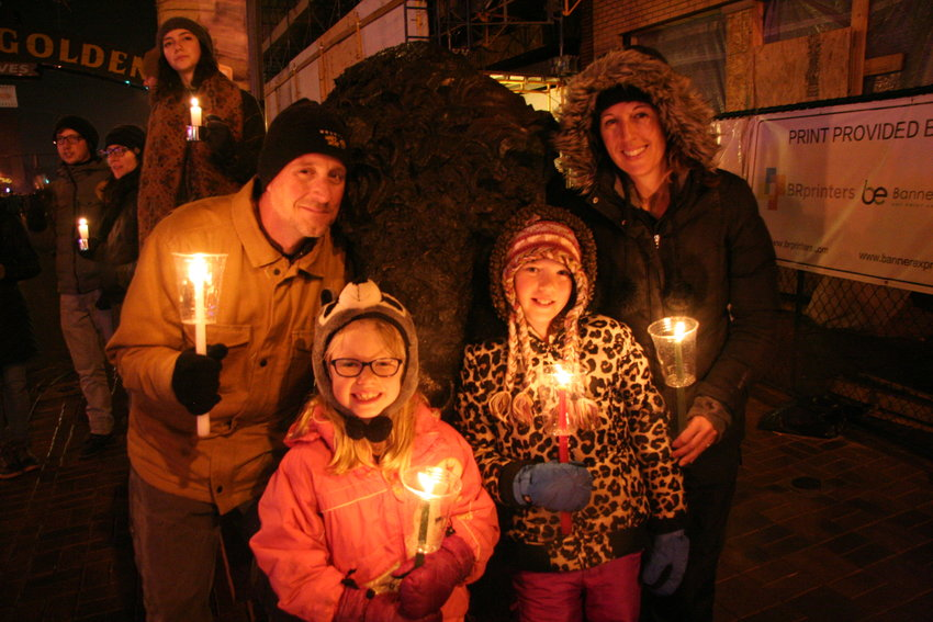 Matt, Melissa, 7, Charlotte, 9, and Amelia Deleeuw pose with candles in front of the buffalo sculpture on Washington Avenue, waiting for the candlelight procession to make its way to them. 