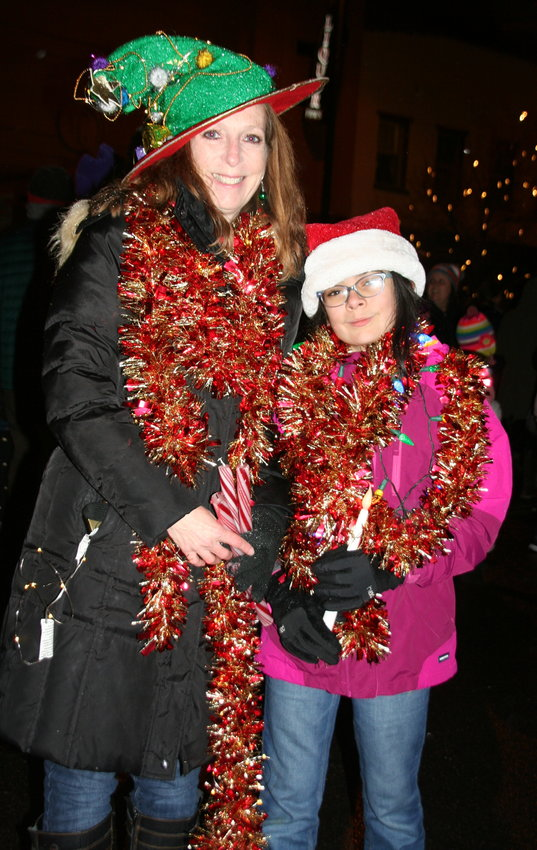 Decked out in festive garland, Goldenites Lauree Valverde and her daughter Ruby, 11, make their way down Washington Avenue during the Candlelight Walk on Nov. 30.