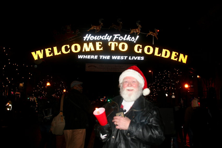 Tom Maloney, of unincorporated Golden, stops for a photo underneath the Howdy Folks arch on Washington Avenue during the Candlelight Walk on Nov. 30.