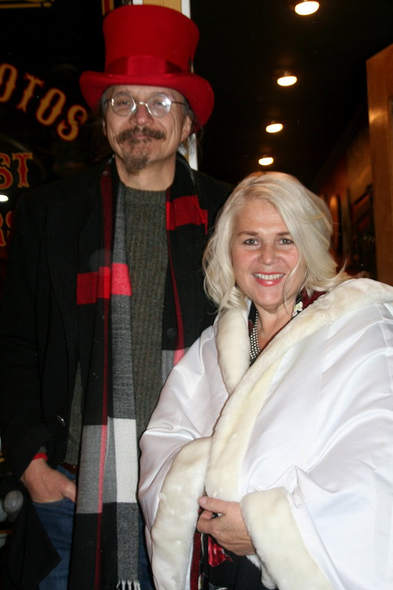 Joe Mierwa and his wife Suzanne Restle, owner of Oh! Susanna Vintage Photo Parlor, stand outside their shop at 1117 Washington Ave., greeting participants of the Candlelight Walk as they pass by on Nov. 30.