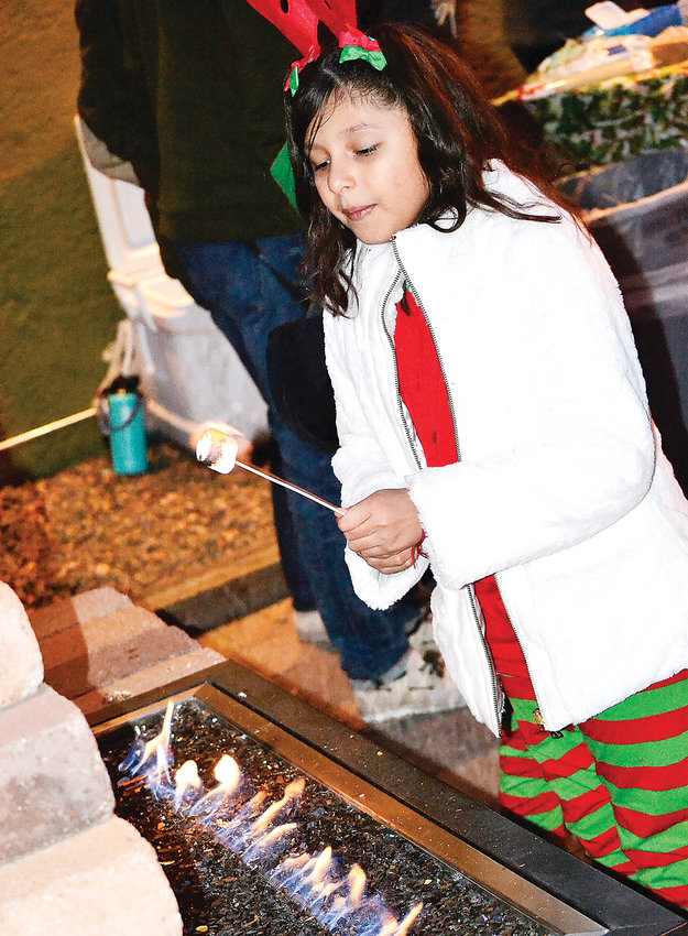 Bryanna Ruiz-Cazon, 8, roasts a marshmallow at a s'mores-making station during Wheat Ridge's Christmas celebration.
