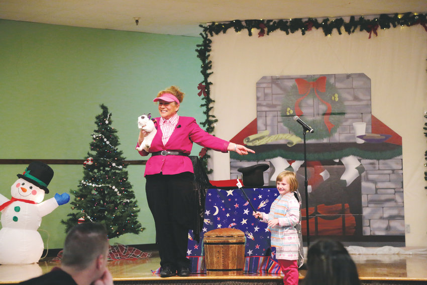 Magician Connie Elstun entertains children at the Santa Breakfast with a show including a live rabbit.
