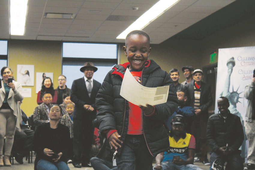 After receiving his citizenship certificate, Griffin Walugembe smiles down at the document.