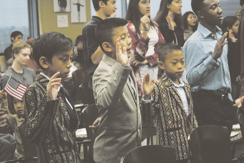The group of young new citizens rises to say the Oath of Allegiance and pledge to honor the United States.