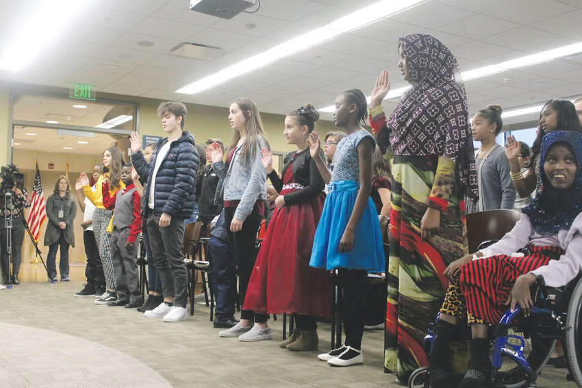 A group of 51 children are repeat an oath of allegiance prior to becoming U.S. citizens through the process of naturalization Nov. 30 in Centennial.