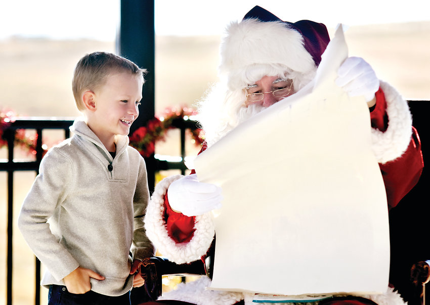 Tyler Nelson shares his letter to Santa with Santa Claus during the Highlands Ranch Holiday Celebration on Dec. 1. After arriving on a Littleton Fire Rescue truck, Santa visited with children throughout the day.