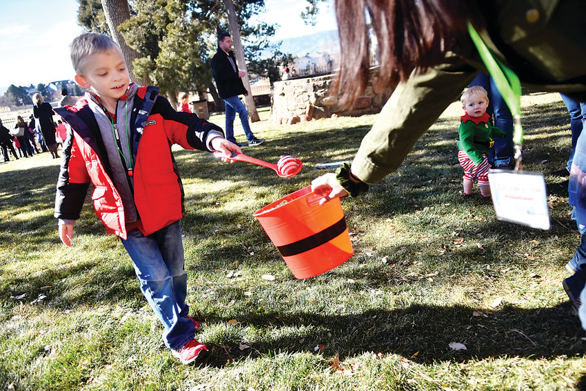 Alex Johnson, 6, finishes an ornament relay race in the backyard of the Highlands Ranch Mansion during the Holiday Celebration. In addition to visiting with Santa, some of the activities for kids included face painting, letters to Santa, a pine cone toss, pin the nose on Rudolph and snowman bowling.